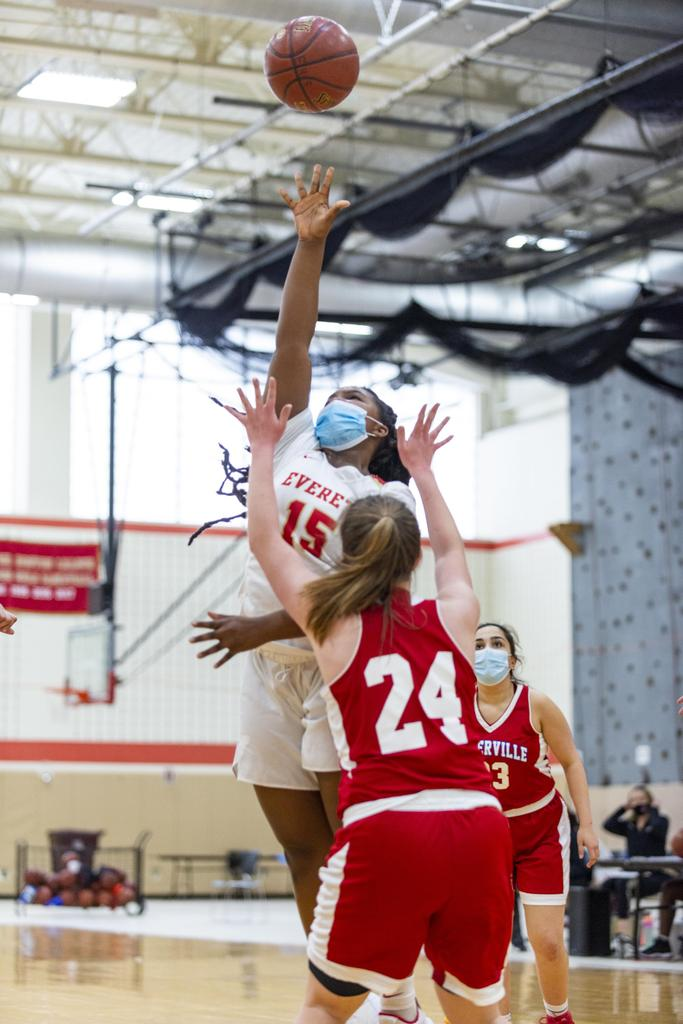 A player attempts a shot over the outstretched arms of a defender