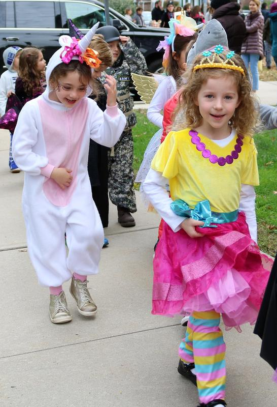Lincoln School kindergartners smile and show off Halloween costumes during parade.