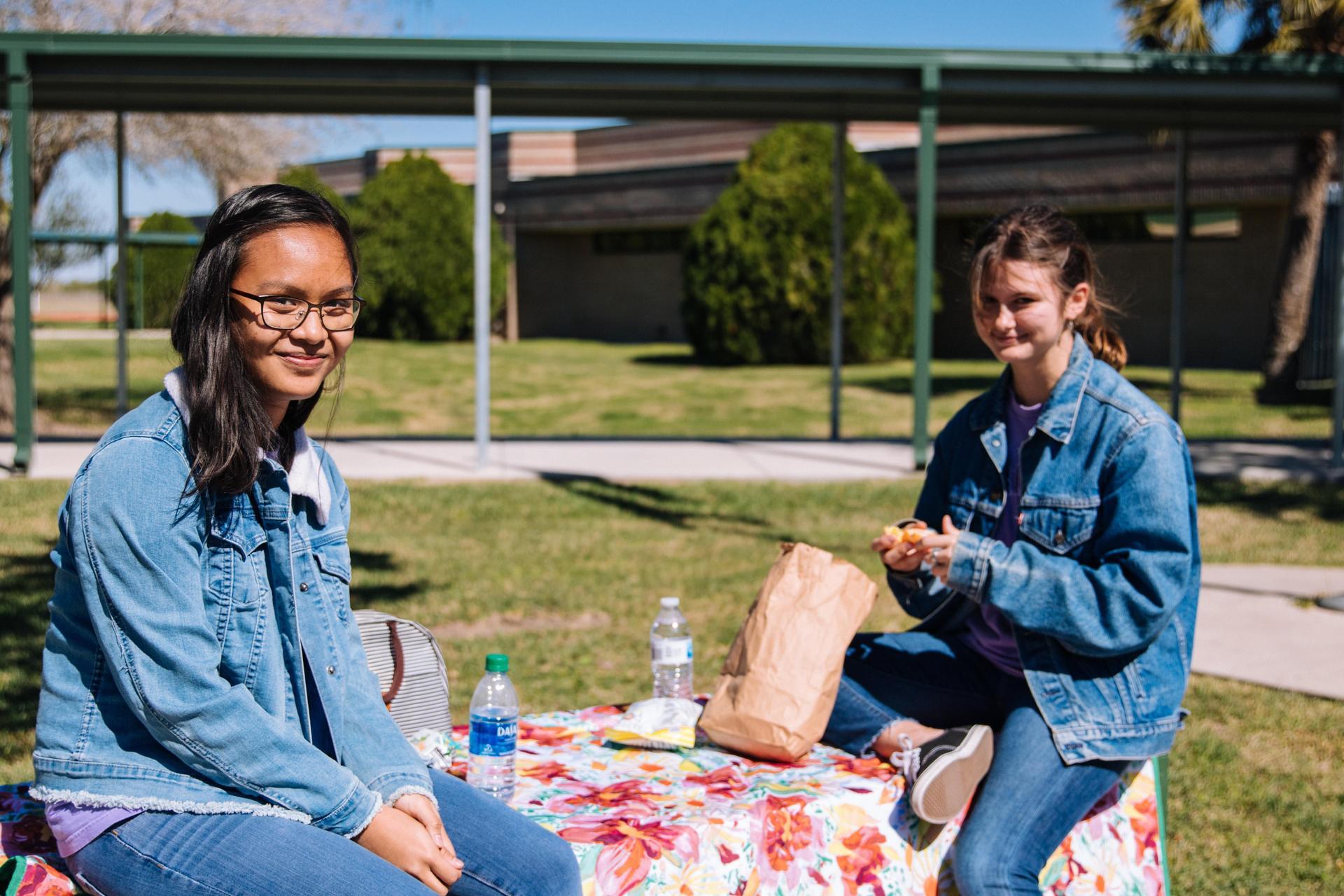 girls eating school lunch outside