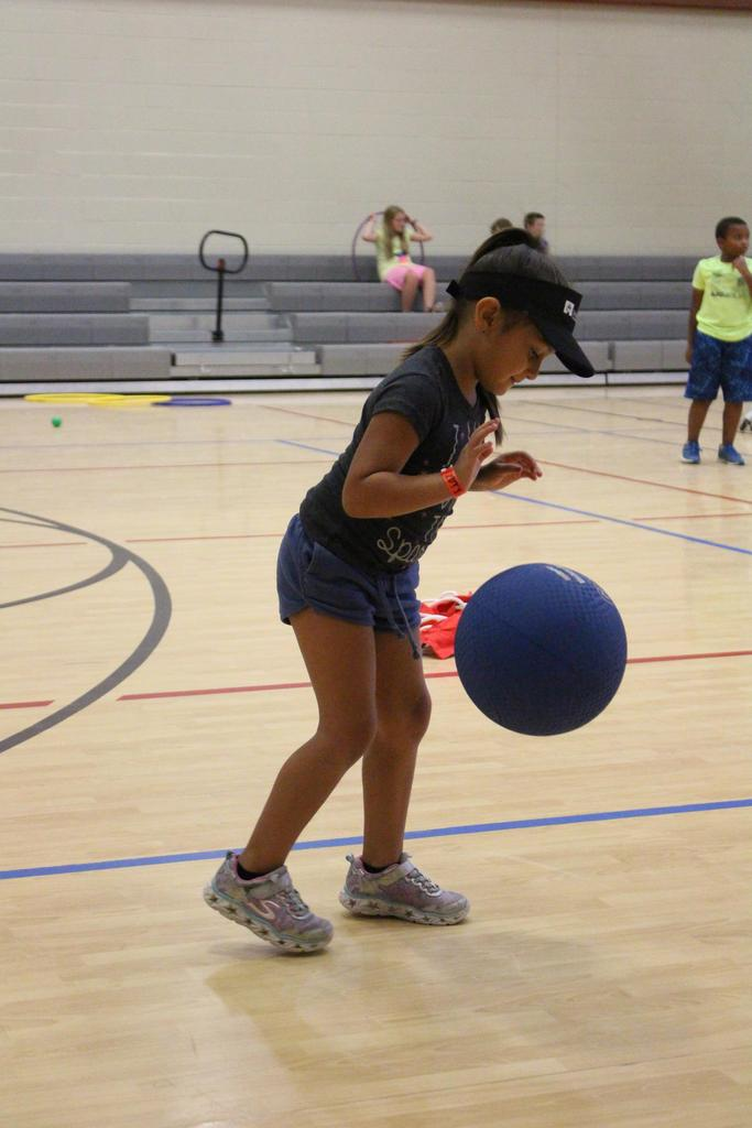 Aunalicia Cisneros practices her dribbling skills during Camp Good Sam recreation time in the Jacob's Well Elementary School Gymnasium.