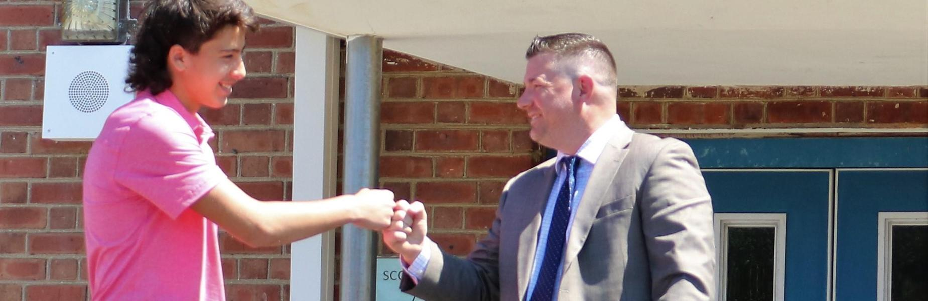 Photo of Edison principal Dr. Matthew Bolton fist bumping 8th grader during promotion ceremony.
