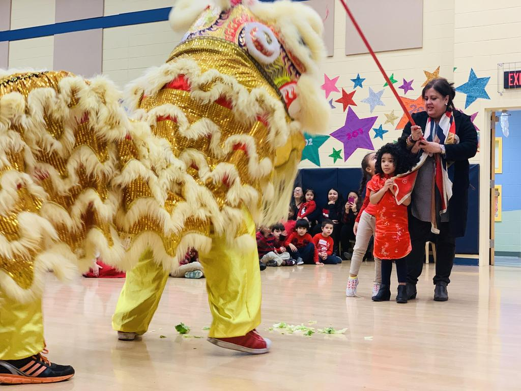 Principal Birne with a a girls holding a stick at the large yellow Chinese Dragon