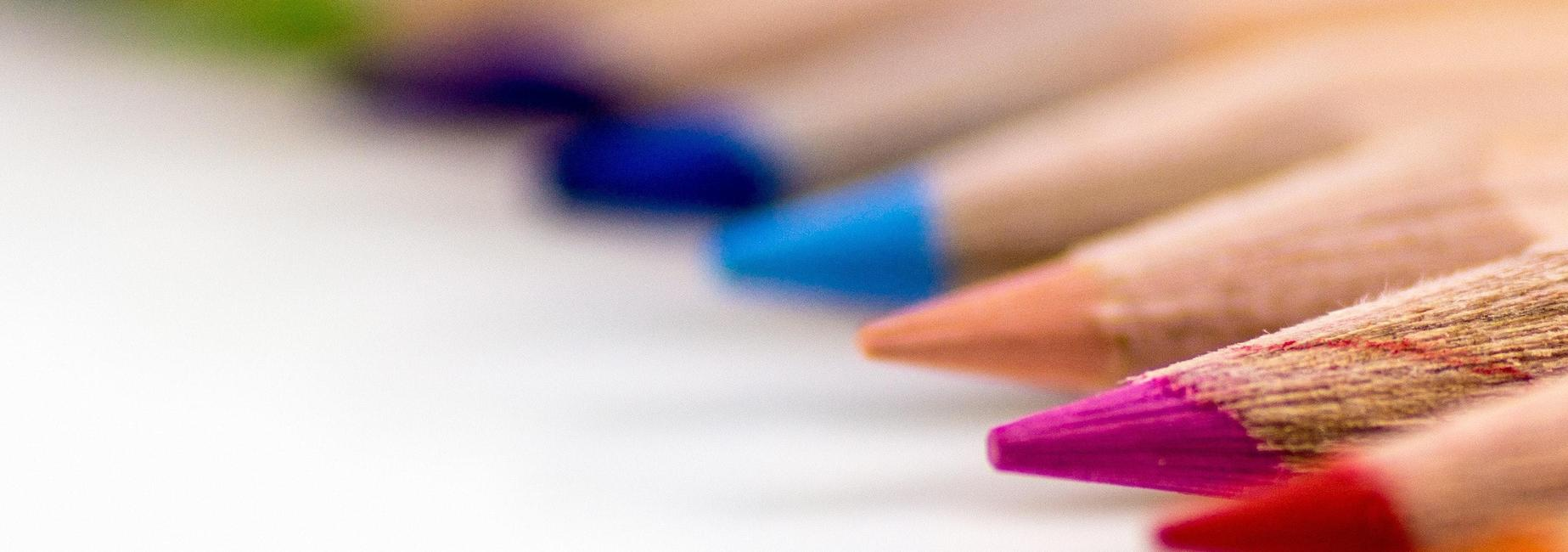 sharpened colored pencils laying down on white surface, caption reads