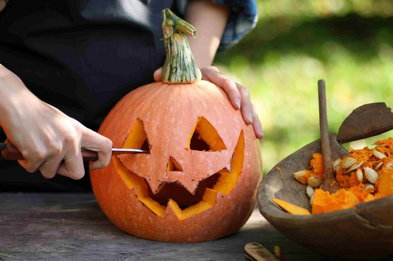 A person carving a pumpkin. Photo source: alexkich/Getty Images