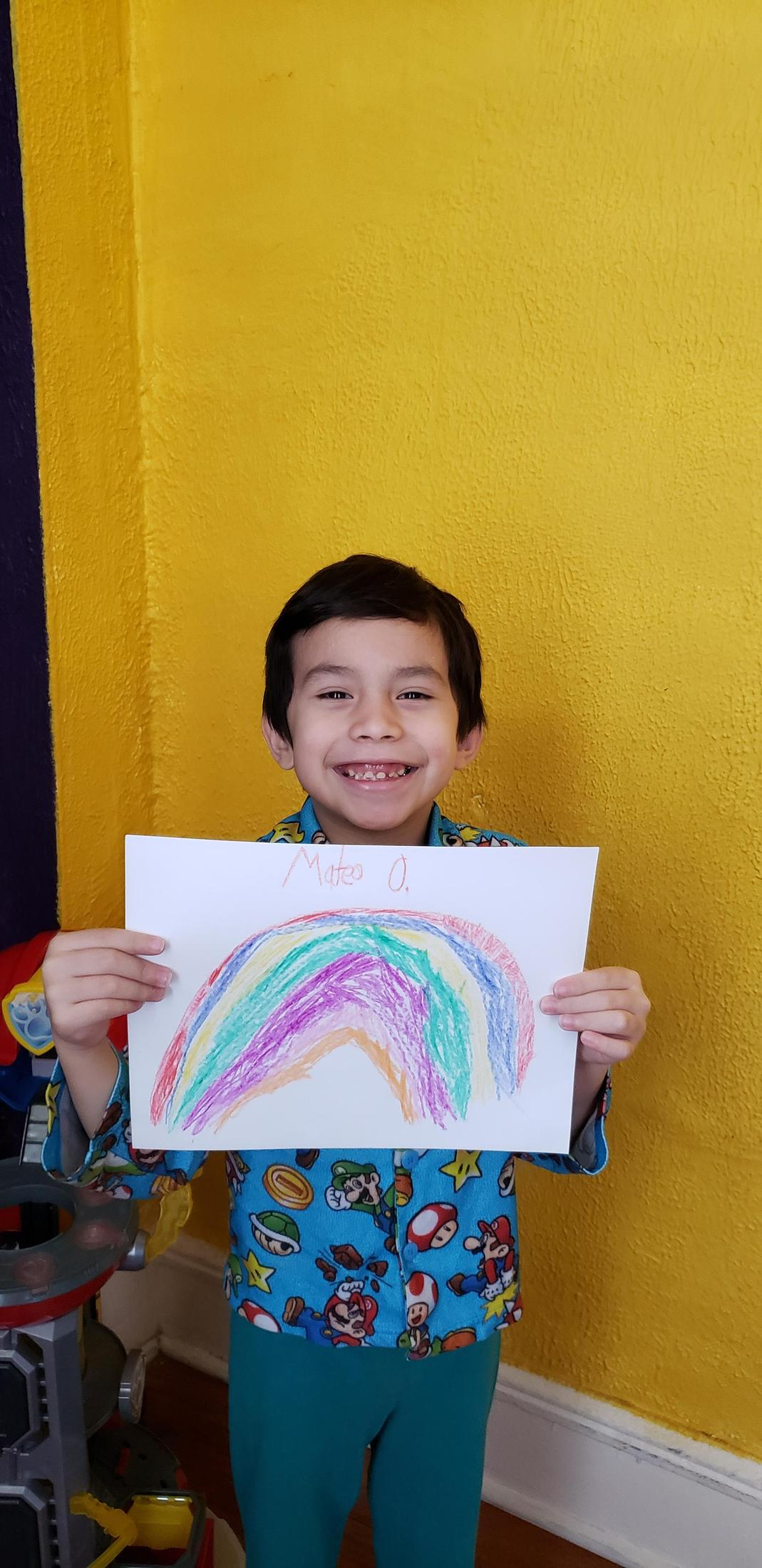 boy showing off his rainbow drawing