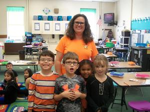 A staff member and students wear orange for