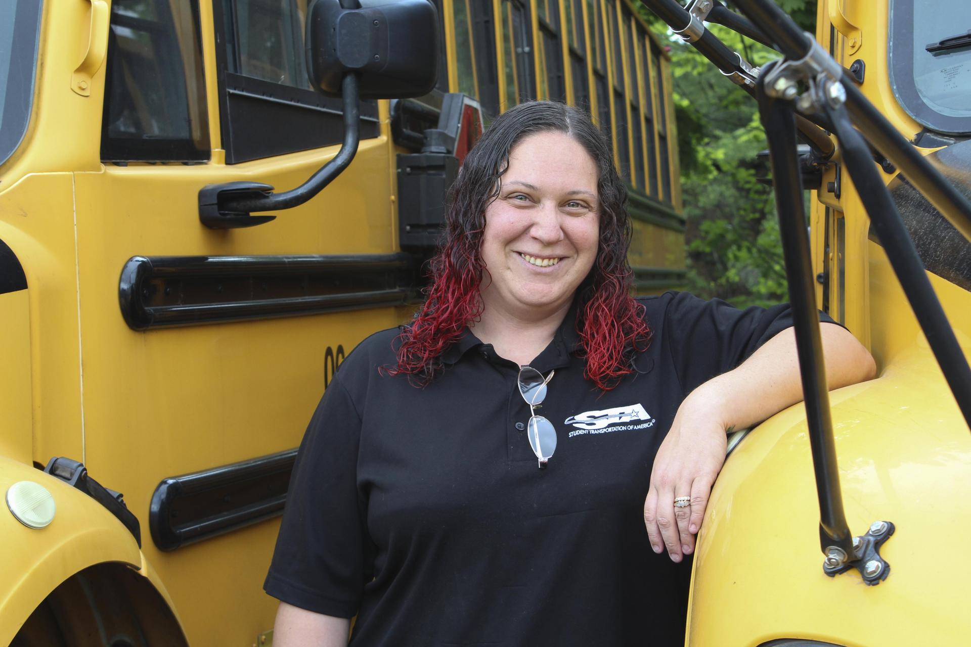 Bus driver posing next to school bus