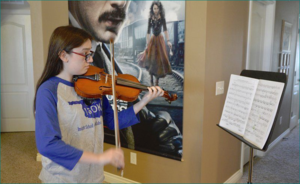 Tenth-grader Erika Maples plays her violin at her north Norman home. Maples is a member of Sooner Strings and attends public school online through Insight School of Oklahoma.  Joy Hampton / The Transcript