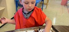 A boy playing with farm animals in chocolate pudding like it is mud
