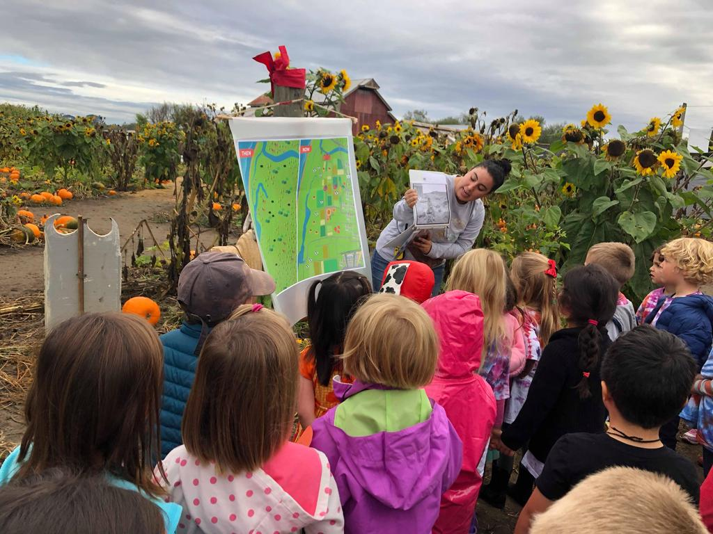 Group of children listening to an adult explain the history of the pumpkin patch