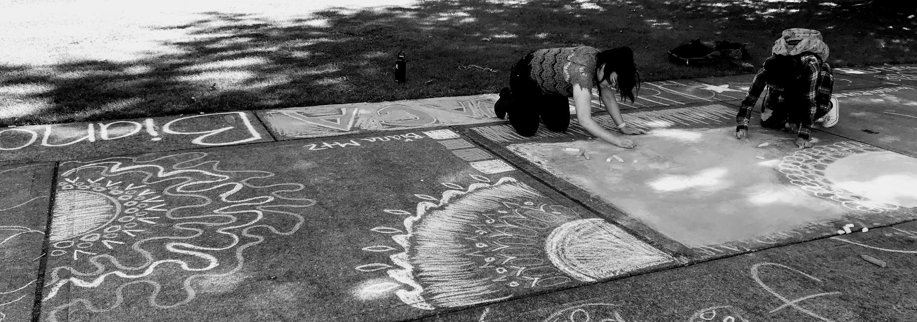 Students drawing with chalk at awards afternoon