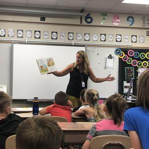 Mrs. Engbers reads the book to her students.
