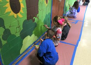 Second and third graders at Jefferson Elementary School help to transform school hallways into a magical scene of the many events that take place each year.  Students are pictured here painting the mural.