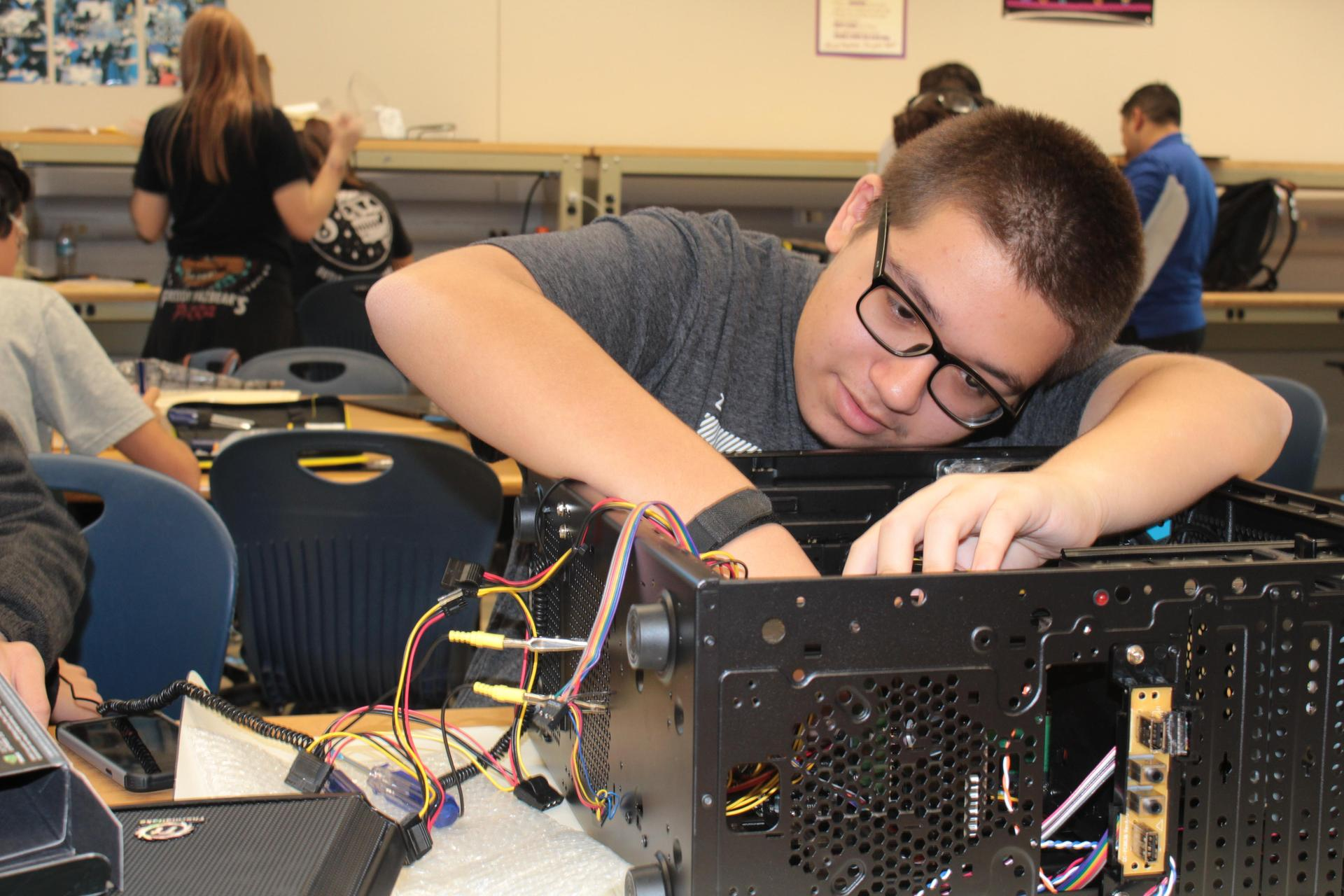 Student working on putting a PC tower back together