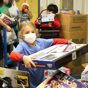 dyer student helps unload boxes of toys