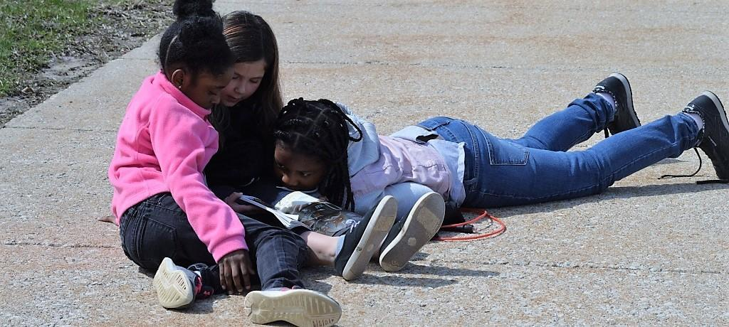 Girls reading outdoors