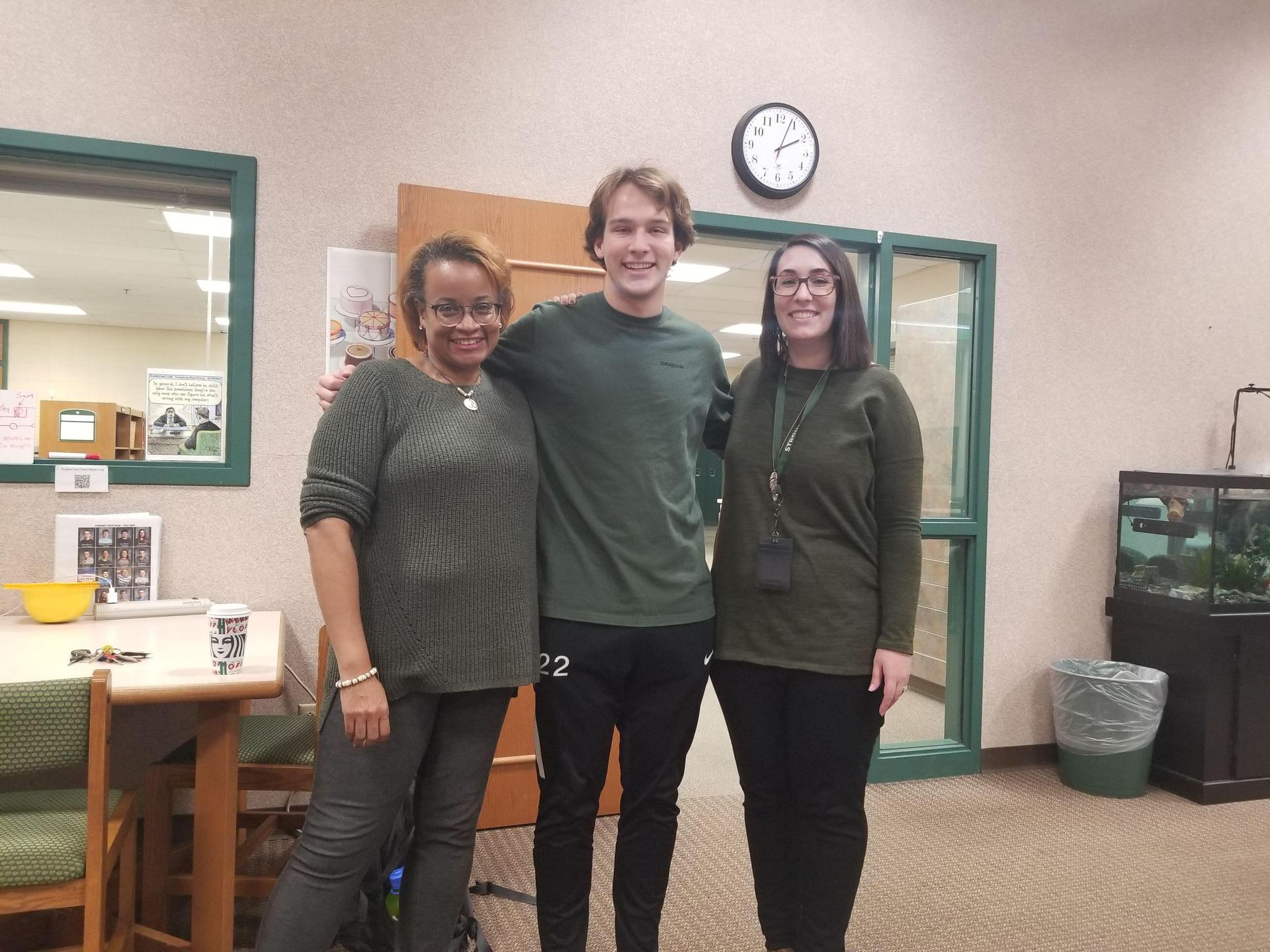 Two teachers posing with a student. All three are wearing green.