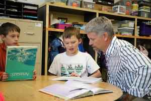 Mr. Geygan reading with 2 students