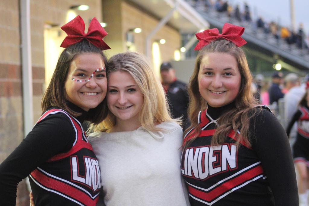 Two cheerleaders and one female student smiling