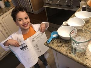 by holding his instruction booklet proudly with ice supplies