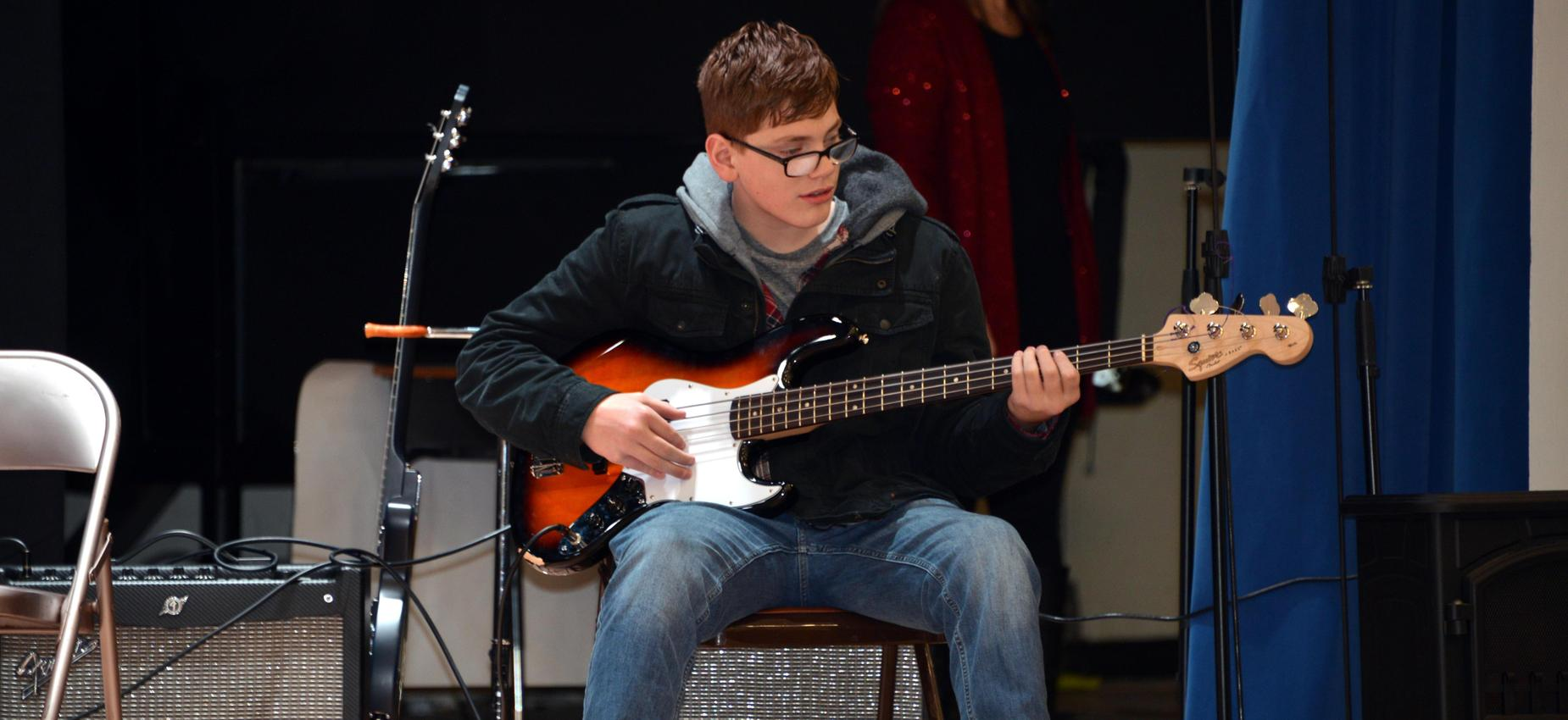 Student sitting and playing guitar