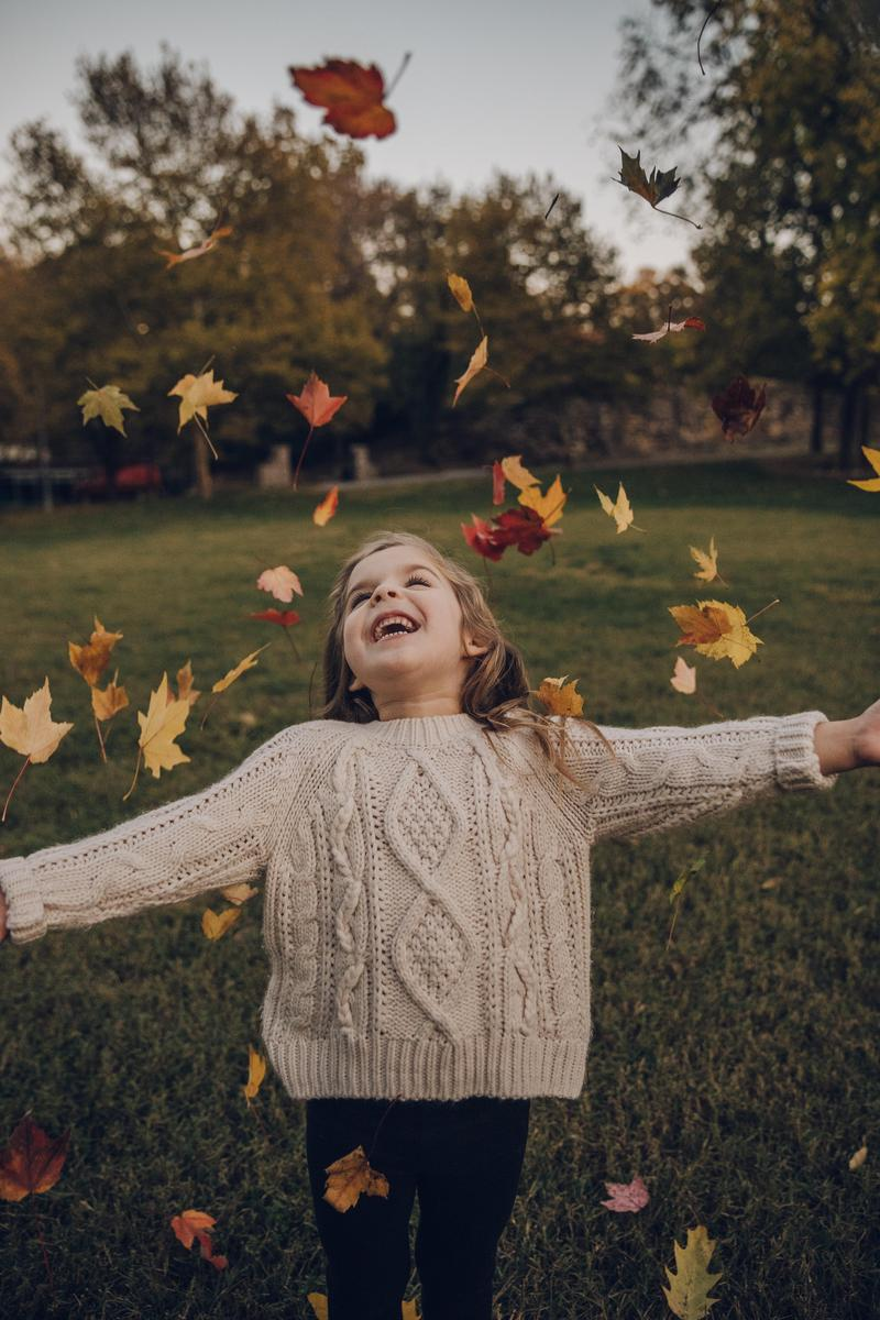 A girl throwing leaves