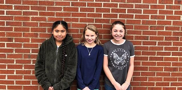 three girls standing against brick wall