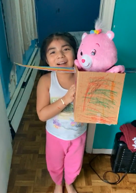 Girl proudly showing her box airplane with her pink carebear
