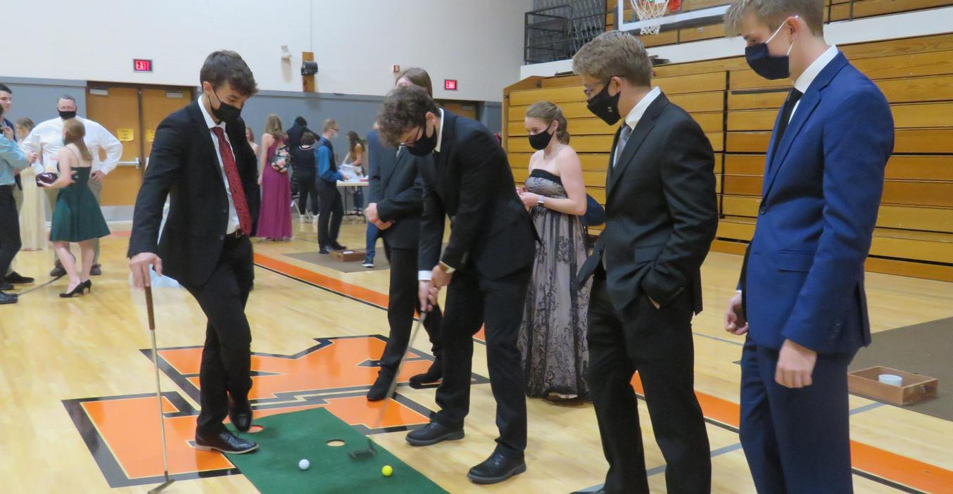 Guys practice putts at the senior 2021 prom.