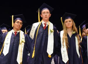 Three high school students wearing graduation caps and gowns.
