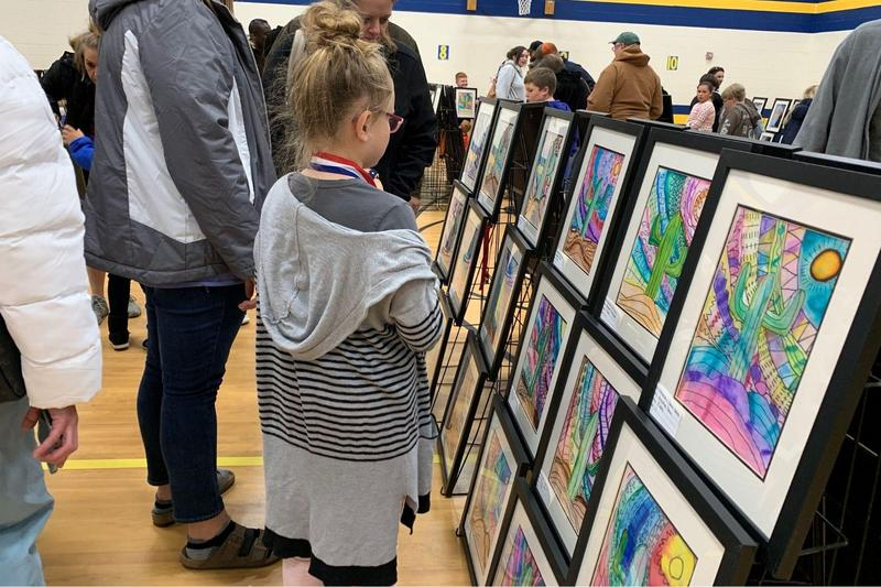 student looks at artwork during upland art show
