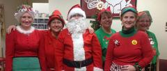 Employees smiling dressed in holiday gear.