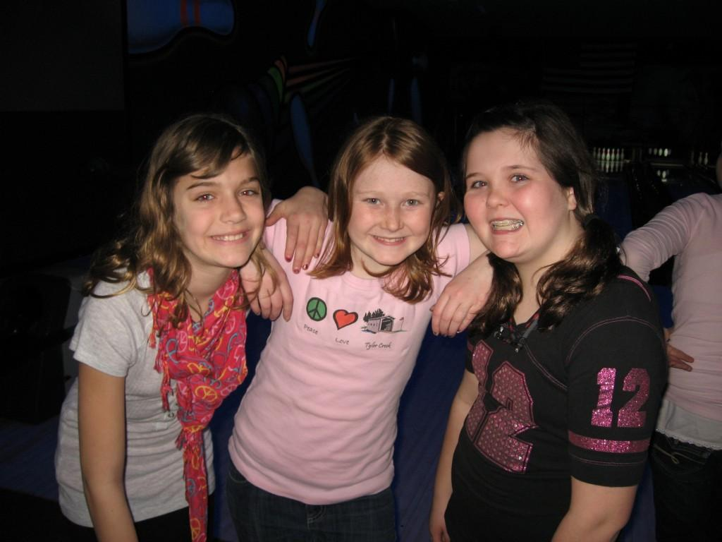 three girls pose for camera at bowling alley
