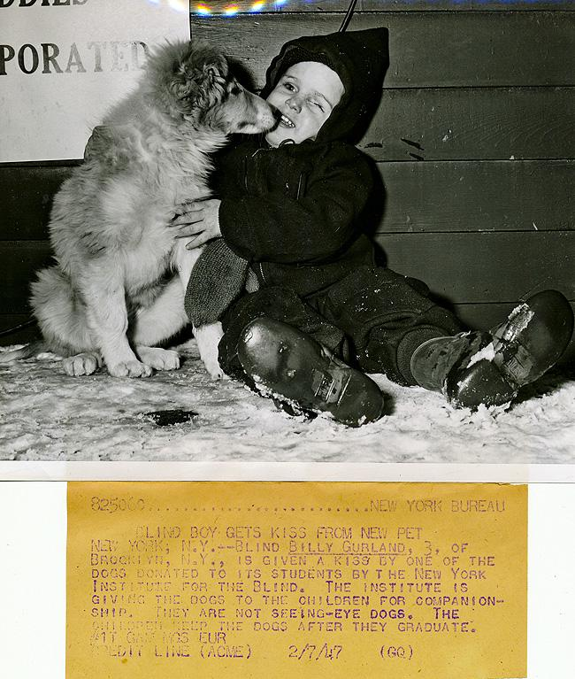 1947 image of winter dressed child sitting in the snow being kissed by his dog.