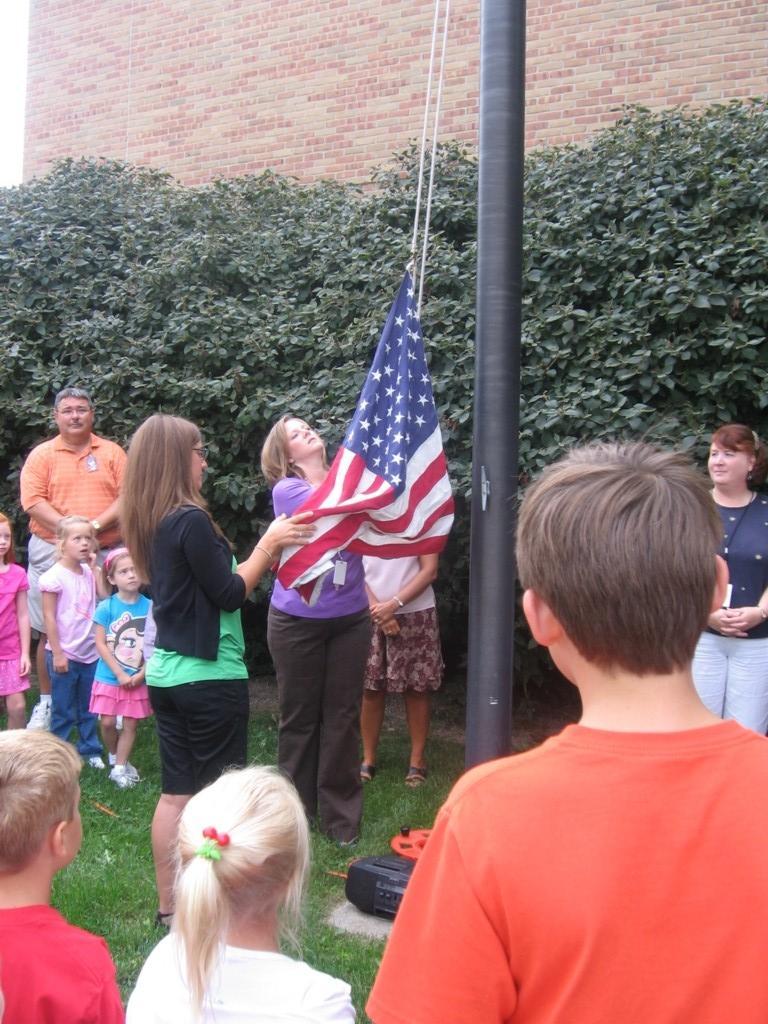 principal raises flag outside as students look on