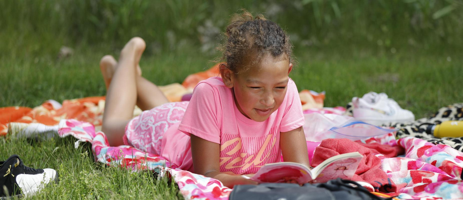 Girl reading on floral blanket outside