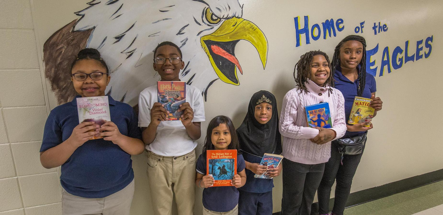 Students standing with books in front of mural
