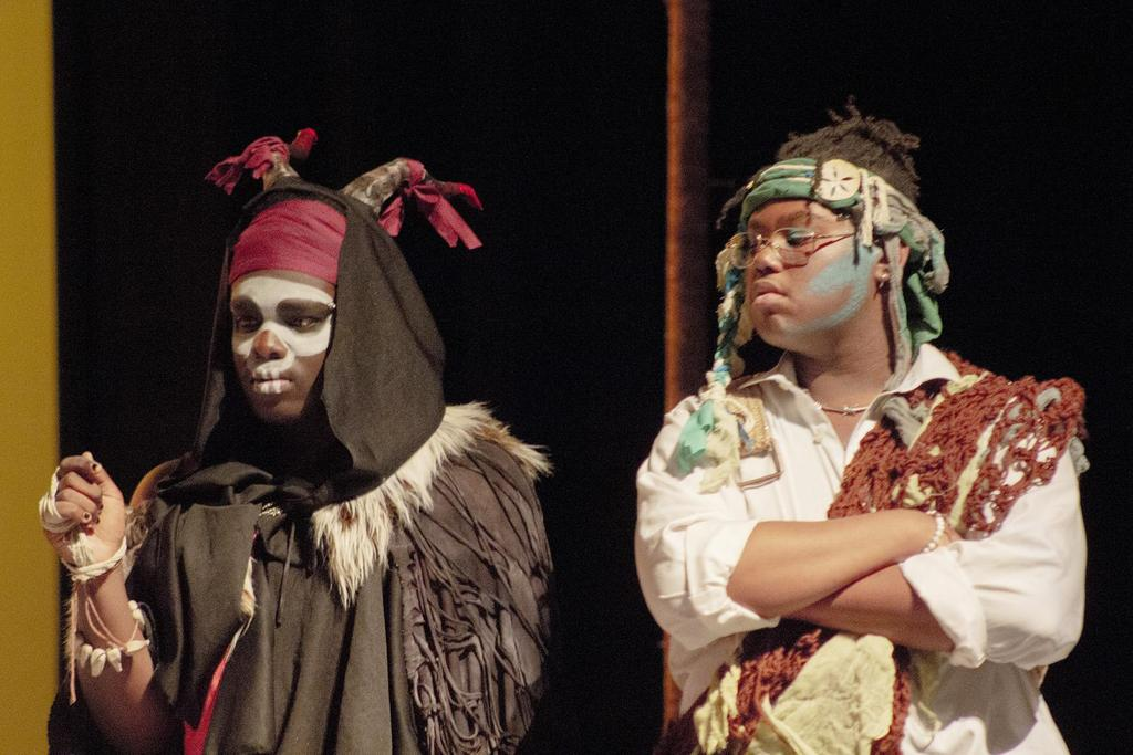 Two cast members act out a scene, both in elaborate costumes