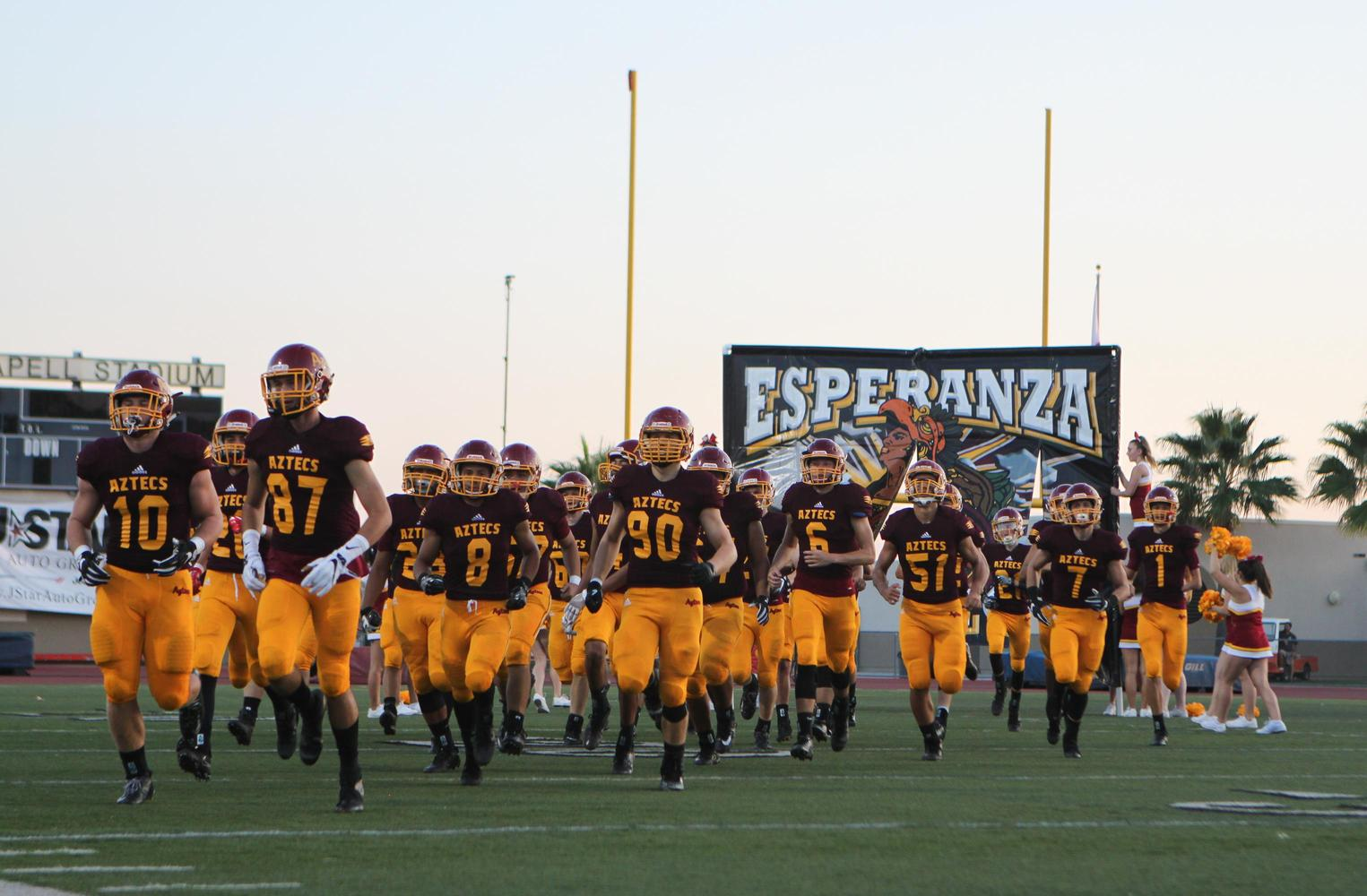 Esperanza's football team running on the field.