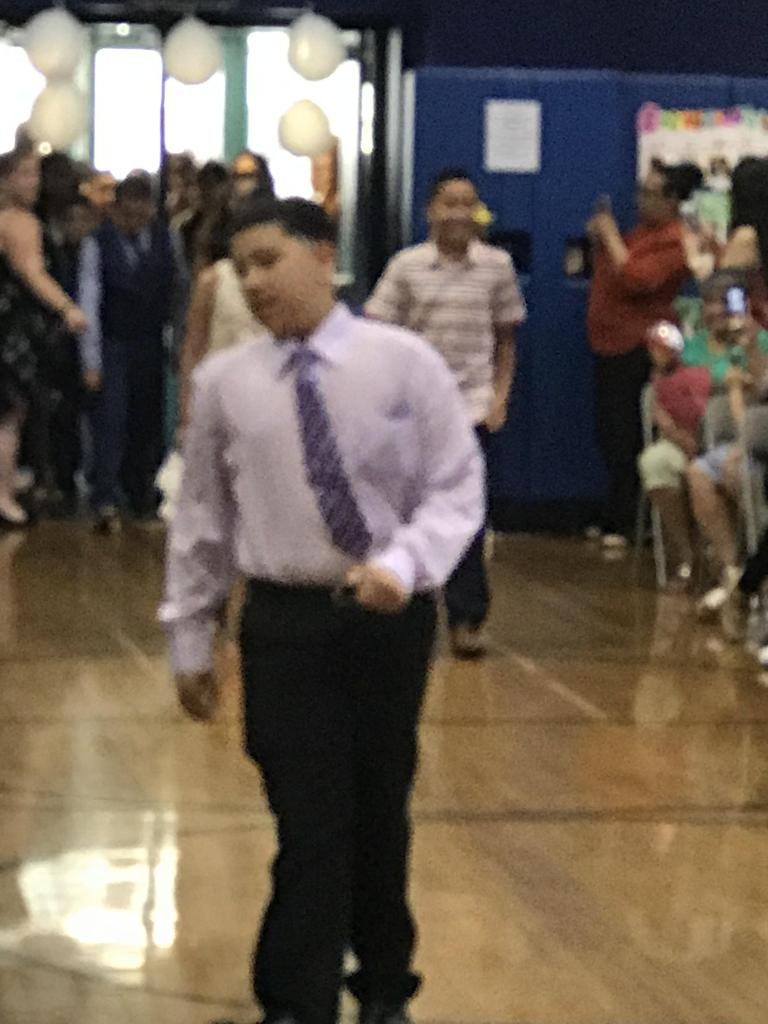 close up of boy with tie walking into gym