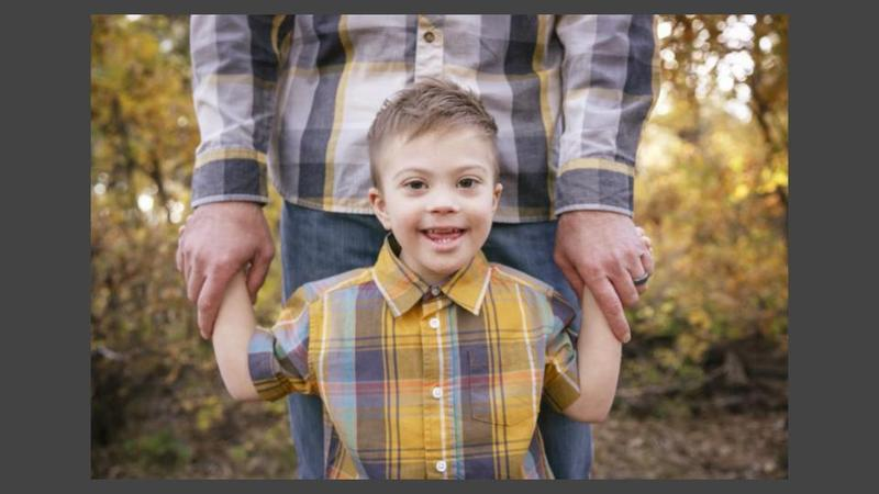 A smiling boy with down syndrome holding a parents hands