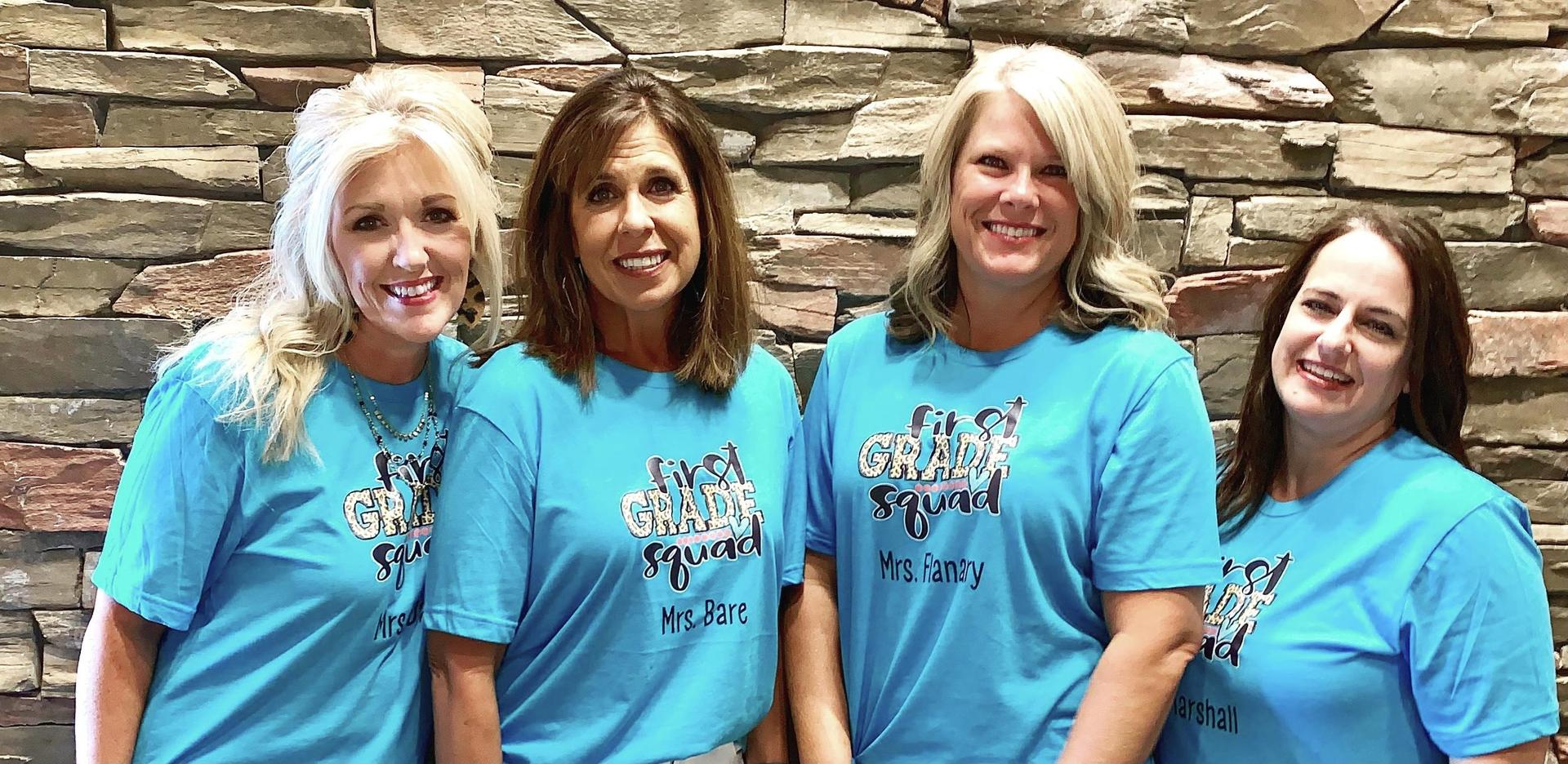 Four 1st grade teachers standing together by a stone wall.