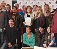 The mayor displays the CTE proclamation, surrounded by students.