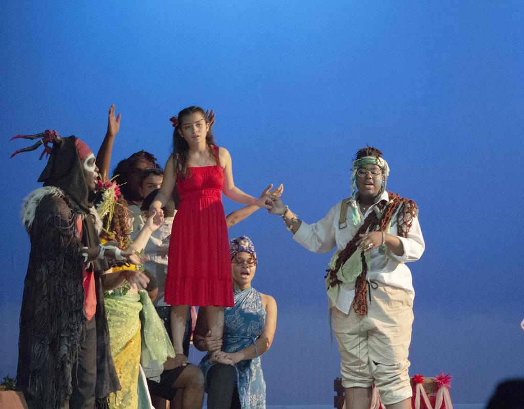 A member of the cast stands on the knees of two others, while a third member of the cast holds her hand