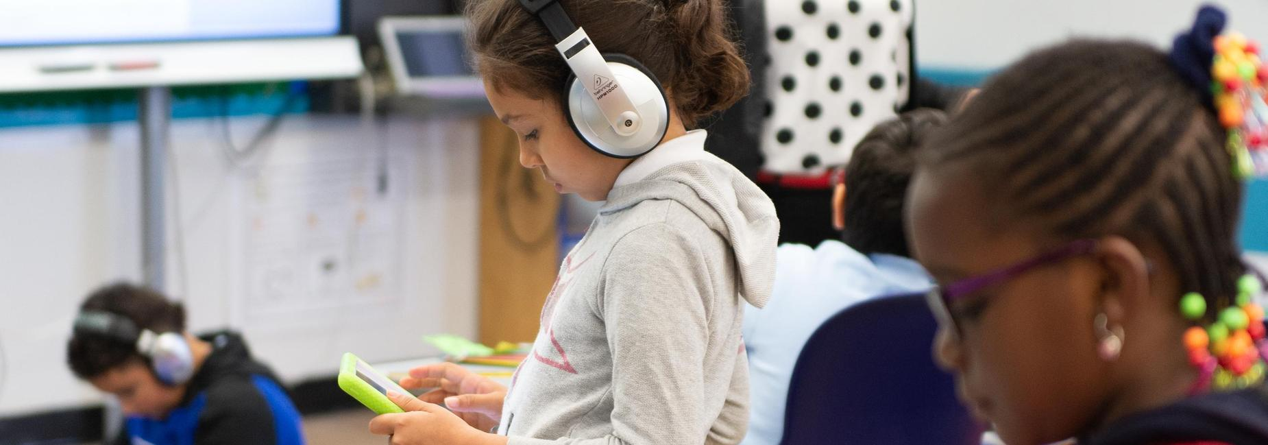 Elementary school students wearing headphones and using tablets.