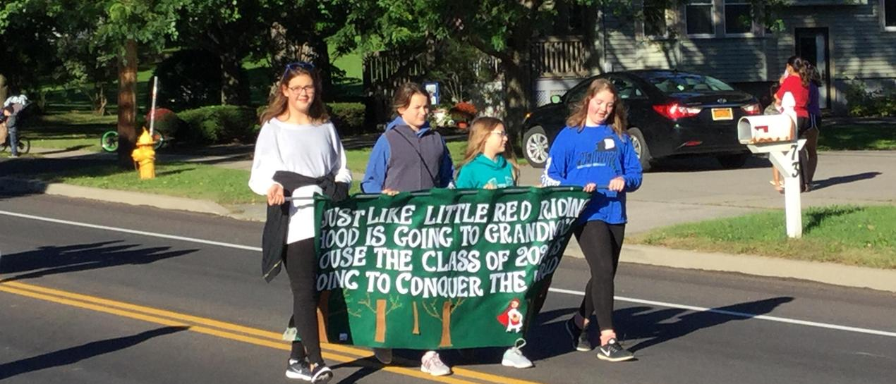 7th graders carrying a banner