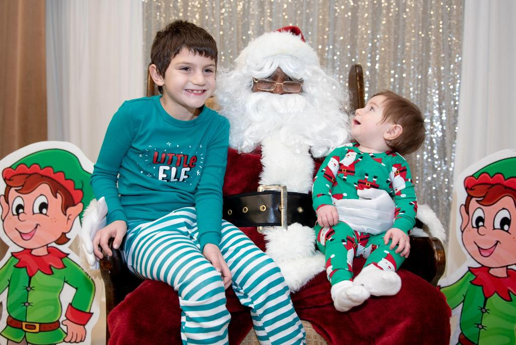 A young student and a toddler visit with Santa, with the toddler looking at Santa in wonder