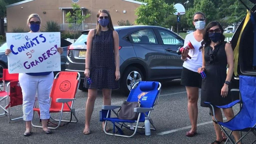 Photo of Jefferson teachers lined up and waving during Grade 5 Clap Out Car Parade