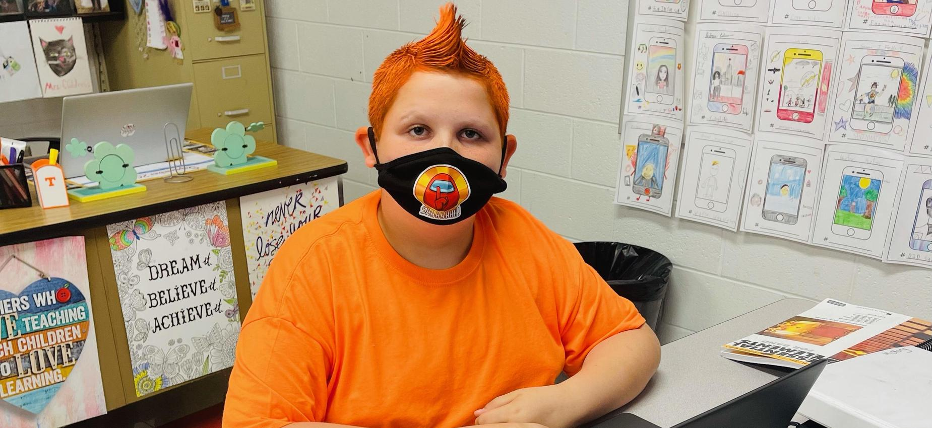 A student wearing orange with orange hair works on a Chromebook.