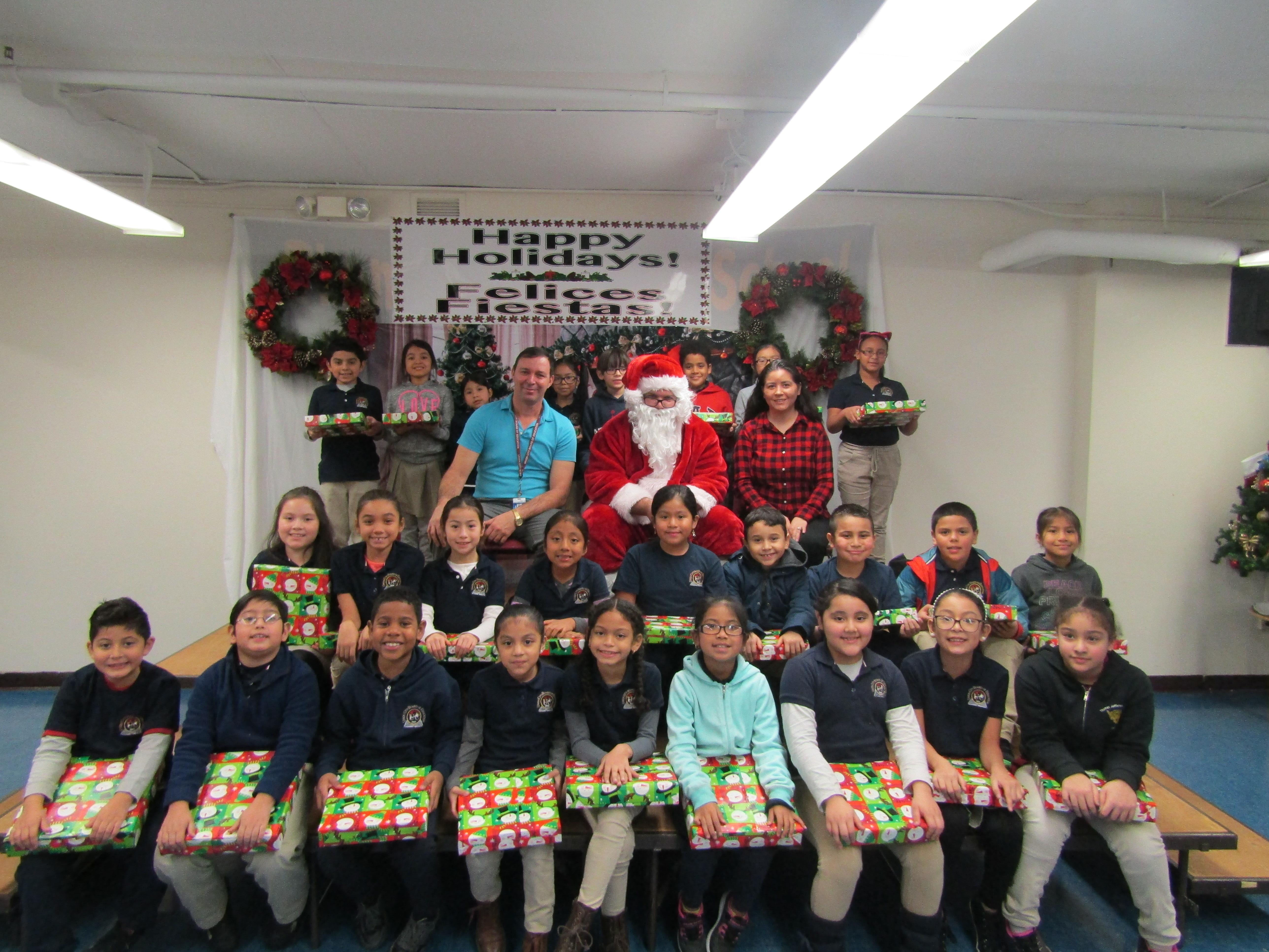 Rm 102 students holding their gifts with their teacher and santa